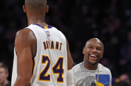 Los Angeles Lakers guard Kobe Bryant, left, talks with boxer Floyd Mayweather Jr. after the Lakers' NBA basketball game against the Phoenix Suns, Sunday, Dec. 28, 2014, in Los Angeles. The Suns won 116-107. (AP Photo/Mark J. Terrill)