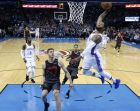 Oklahoma City Thunder forward Paul George, right, goes up for a dunk in front of Portland Trail Blazers forward Meyers Leonard (11) and guard C.J. McCollum, center, in the second half of an NBA basketball game in Oklahoma City, Tuesday, Jan. 22, 2019. (AP Photo/Sue Ogrocki)