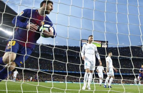 Barcelona's Lionel Messi collects the ball from the goal after Luis Suarez scored the opening goal during a Spanish La Liga soccer match between Barcelona and Real Madrid, dubbed 'el clasico', at the Camp Nou stadium in Barcelona, Spain, Sunday, May 6, 2018. (AP Photo/Manu Fernandez)