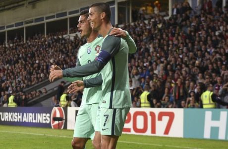 Portugal's Cristiano Ronaldo, right, reacts with Andre Silva, centre, and Andre Gomes, after scoring during World Cup Group B qualifying match between Latvia and Portugal at the Skonto Stadium in Riga, Latvia, Friday, June 9, 2017. (AP Photo/Roman Koksarov)