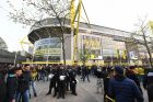 Police officers and fans stand in front of the Signal Iduna Park in Dortmund, Germany, Tuesday, April 11. The first leg of the Champions League quarter final soccer match between Borussia Dortmund and AS Monaco had been cancelled to an explosion. (AP Photo/Bernd Thissen/dpa via AP