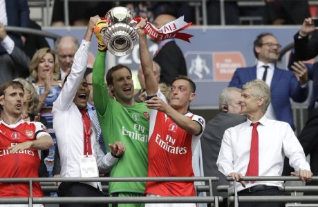Arsenal team manager Arsene Wenger, right, watches as players celebrate with the trophy after winning the English FA Cup final soccer match between Arsenal and Chelsea at the Wembley stadium in London, Saturday, May 27, 2017. (AP Photo/Matt Dunham)