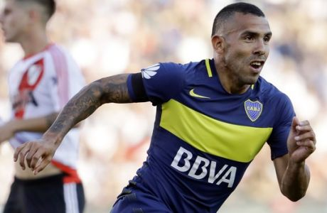 """FILE - In this Dec. 11, 2016 file photo, Boca Juniors' forward Carlos Tevez celebrates scoring against River Plate during a local tournament soccer match in Buenos Aires, Argentina. The governing body of Chinese soccer plans a series of measures in response to what is termed """"irrational"""" spending by clubs on transfer fees and player salaries, amid concerns that foreign stars are crowding out local talent and harming the country's goal of becoming a global force in the sport. Spending by Chinese clubs on players such as Argentina's Carlos Tevez has drawn global attention, raising fears among some that domestic players will be denied opportunities. (AP Photo/Natacha Pisarenko, File)"""