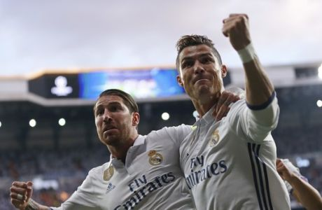 Real Madrid's Cristiano Ronaldo celebrates with Real Madrid's Sergio Ramos, left, after scoring the opening goal during the Champions League semifinals first leg soccer match between Real Madrid and Atletico Madrid at Santiago Bernabeu stadium in Madrid, Spain, Tuesday May 2, 2017. (AP Photo/Daniel Ochoa de Olza)