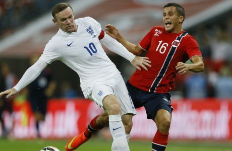 England's Wayne Rooney, left, clashes with Norway's Omar Elabdellaoui during the international friendly soccer match between England and Norway at Wembley Stadium in London, Wednesday, Sept. 3, 2014. (AP Photo/Kirsty Wigglesworth)