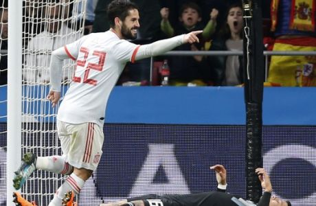 Spain's Isco Alarcon celebrates scoring his side's third goal as Argentina's Marcos Rojo lies defeated on the pitch during the international friendly soccer match between Spain and Argentina at the Wanda Metropolitano stadium in Madrid, Spain, Tuesday, March 27, 2018. (AP Photo/Francisco Seco)