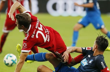 Hoffenheim's Benjamin Huebner, right, and Bayern's Thomas Mueller challenge for the ball during a German first division Bundesliga soccer match between TSG 1899 Hoffenheim and Bayern Munich in Sinsheim, Germany, Saturday, Sept. 9, 2017. (AP Photo/Michael Probst)