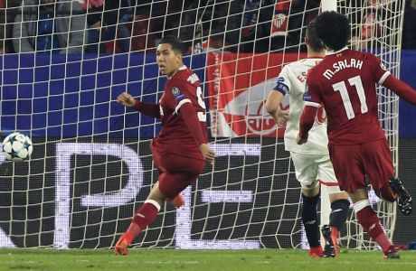Liverpool's Roberto Firmino, left, scores his side's third goal during a Champions League group E soccer match between Sevilla and Liverpool, at the Ramon Sanchez Pizjuan stadium in Seville, Spain, Tuesday, Nov. 21, 2017. (AP Photo/Miguel Morenatti)