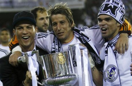 Real Madrid's Portuguese players Cristiano Ronaldo, left,  Fabio Coentrao, centre and Pepe celebrate with the trophy after Real Madrid won the final of the Copa del Rey between FC Barcelona and Real Madrid at the Mestalla stadium in Valencia, Spain, Wednesday, April 16, 2014. (AP Photo/Alberto Saiz)