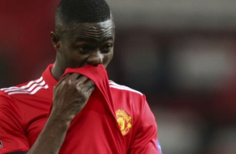 Manchester United's Eric Bailly wipes his face as he walks from the pitch after the end of the Champions League round of 16 second leg soccer match between Manchester United and Sevilla, at Old Trafford in Manchester, England, Tuesday, March 13, 2018. Sevilla won the game 2-1 and go through to the quarterfinals .(AP Photo/Dave Thompson)