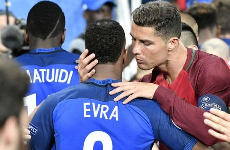 Portugal's Cristiano Ronaldo, right, embraces France's Patrice Evra at the end of  the Euro 2016 final soccer match between Portugal and France at the Stade de France in Saint-Denis, north of Paris, Sunday, July 10, 2016. Portugal won 1-0. (AP Photo/Martin Meissner)