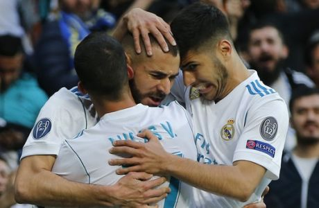 Real Madrid's Karim Benzema is congratulated by his teammates Lucas Vazquez, left, and Marco Asensio, right, after scoring their side's first goal during the Champions League semifinal second leg soccer match between Real Madrid and FC Bayern Munich at the Santiago Bernabeu stadium in Madrid, Spain, Tuesday, May 1, 2018. (AP Photo/Paul White)