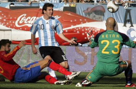 Argentina's Leonel Messi, center, scores as Spain's players Jose Manuel Reina, right, and Gerard Pique fail to block during a friendly soccer match in Buenos Aires,  Argentina, Tuesday, Sept. 7, 2010. (AP Photo/Alberto Raggio)