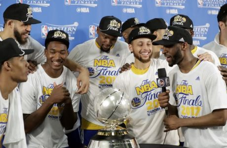 Golden State Warriors' Kevin Durant, center left, and Stephen Curry, center right, celebrate with teammates after their 129-115 win over the San Antonio Spurs in Game 4 of the NBA basketball Western Conference finals, Monday, May 22, 2017, in San Antonio. (AP Photo/Eric Gay)