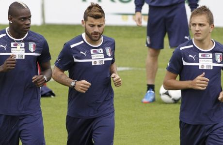 In this photo mada available Monday, May 28, 2012, Italy's Domenico Criscito, right, looks at teammates Mario Balotelli, left, and Antonio Nocerino during a training session at the Coverciano sports center, near Florence, Italy, Saturday, May 26, 2012. Italy and Zenit St Petersburg defender Criscito was placed under investigation by Italian police, Monday, May 28, 2012, just a week before the national team leaves for the European Championship in Poland and Ukraine, as part of a wide-ranging investigation into match-fixing in football. Italian authorities swept through the Coverciano training site and made more than a dozen arrests elsewhere. News reports said also Lazio captain Stefano Mauri was among those arrested while the coach of Italian champion Juventus, Antonio Conte, was placed under investigation for alleged wrongdoing while coach of Siena. (AP Photo/Fabrizio Giovannozzi)