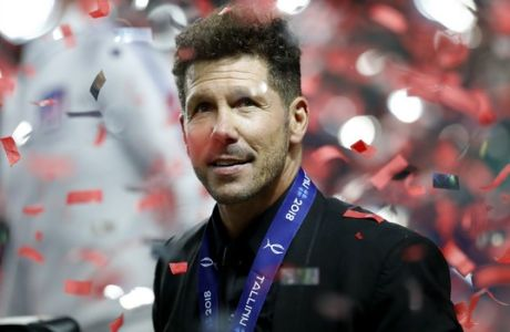 Atletico's head coach Diego Simeone is seen through flying confetti after the UEFA Super Cup final soccer match between Real Madrid and Atletico Madrid at the Lillekula Stadium in Tallinn, Estonia, Wednesday, Aug. 15, 2018. (AP Photo/Pavel Golovkin)