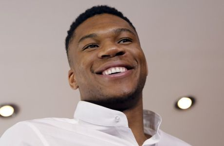 NBA star Giannis Antetokounmpo, smiles during a press conference by Greece's Tourism Ministry to promote his native Greece, in Athens, on Friday, June 29, 2018. Antetokounmpo, whose parents immigrated to Greece from Nigeria, said he always encourages his friends to visit but his favorite part of the country is Athens, where he grew up. (AP Photo/Petros Giannakouris)