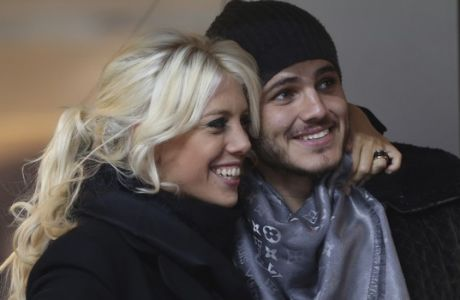 Inter Milan forward Mauro Icardi, of Argentina, is flanked by Argentine model Wanda Nara as they sit in the stands prior to a Serie A soccer match between Inter Milan and Chievo, at the San Siro stadium in Milan, Italy, Monday, Jan.13, 2014. (AP Photo/Luca Bruno)