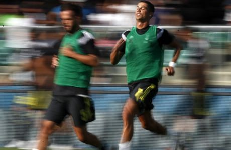 In this photo taken with slow shutter speed, Juventus' Cristiano Ronaldo, right, and Miralem Pjanic, warm up prior to the Serie A soccer match between Chievo Verona and Juventus, at the Bentegodi Stadium in Verona, Italy, Saturday, Aug. 18, 2018. (AP Photo/Antonio Calanni)
