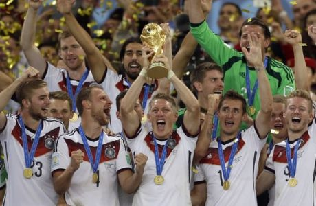 FILE - In this July 13, 2014 file photo Germany's Bastian Schweinsteiger holds up the World Cup trophy as the team celebrates their 1-0 victor over Argentina after the World Cup final soccer match between Germany and Argentina at the Maracana Stadium in Rio de Janeiro, Brazil. FIFA is about to make the World Cup a bigger and, it hopes, richer event even at the cost of lower quality soccer. FIFA President Gianni Infantino hopes his ruling Council will agree Tuesday, Jan. 10, 2017 to expand the 2026 World Cup to 48 nations, playing in 16 groups of three teams. (AP Photo/Natacha Pisarenko, file)