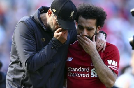 Liverpool manager Juergen Klopp, left, talks to Liverpool's Mohamed Salah at the end of the English Premier League soccer match between Liverpool and Wolverhampton Wanderers at the Anfield stadium in Liverpool, England, Sunday, May 12, 2019. Despite a 2-0 win over Wolverhampton Wanderers, Liverpool missed out on becoming English champion for the first time since 1990 because title rival Manchester City beat Brighton 4-1. (AP Photo/Dave Thompson)