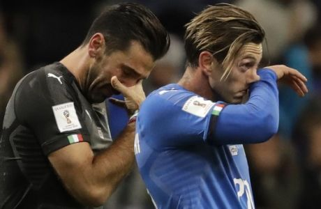 CORRECTS IDENTITY OF PLAYER AT RIGHT Italy's goalkeeper Gianluigi Buffon, left, and Federico Bernardeschi react to their team's elimination in the World Cup qualifying play-off second leg soccer match between Italy and Sweden, at the Milan San Siro stadium, Italy, Monday, Nov. 13, 2017. (AP Photo/Luca Bruno)