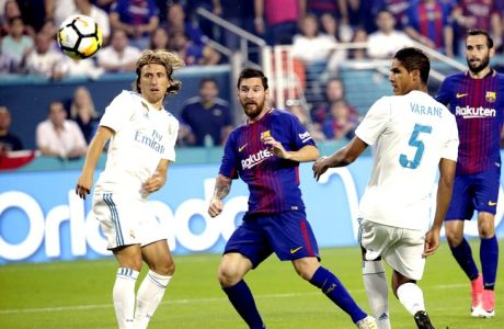 Barcelona's Lionel Messi, center, watches after kicking the ball for a goal as Real Madrid's Luka Modric, left, and Raphael Varane (5) look on during the first half of an International Champions Cup soccer match, Saturday, July 29, 2017, in Miami Gardens, Fla. (AP Photo/Lynne Sladky)