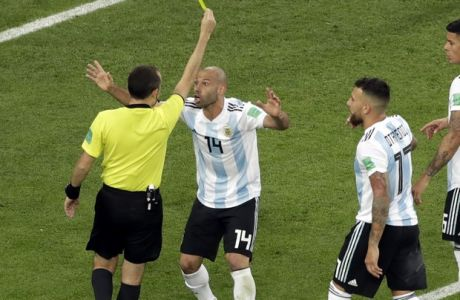 Referee Cuneyt Cakir shows a yellow card to Argentina's Javier Mascherano for a foul in the box during the group D match between Argentina and Nigeria, at the 2018 soccer World Cup in the St. Petersburg Stadium in St. Petersburg, Russia, Tuesday, June 26, 2018. (AP Photo/Michael Sohn)