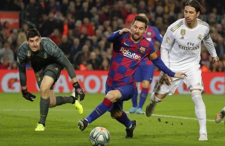 Λιονέλ Μέσι και Σέρχιο Ράμος ερίζουν για την μπάλα υπό το βλέμμα του Τιμπό Κουρτουά, στο πρόσφατο clasico (18/12/2019) της La Liga που ολοκληρώθηκε δίχως τέρματα στο Camp Nou της Βαρκελώνης. (AP Photo/Emilio Morenatti)