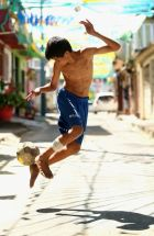 MANAUS, BRAZIL - JUNE 14:  A young boy plays football on the streets outside the stadium ahead of the 2014 FIFA World Cup Brazil Group D match between England and Italy at Arena Amazonia on June 14, 2014 in Manaus, Brazil.  (Photo by Richard Heathcote/Getty Images)