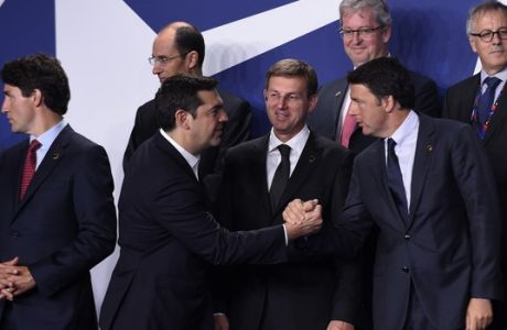 Greek Prime Minister Alexis Tsipras, second from left, shakes hands with Italy's Prime Minister Matteo Renzi as they and other leaders arrive for a NATO family photo at PGE National Stadium in Warsaw, Poland, Friday, July 8, 2016. Slovenia's Prime Minister Miro Cerar watches in the middle. Canadian Prime Minister Justin Trudeau is at left. (AP Photo/Susan Walsh)