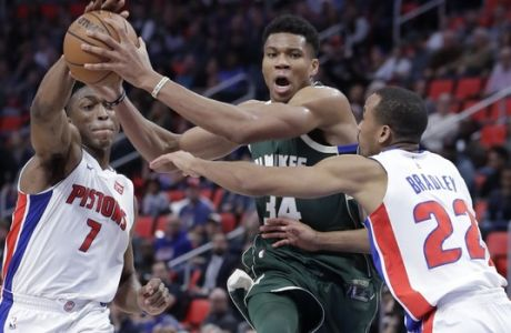 Milwaukee Bucks forward Giannis Antetokounmpo (34) is defended by Detroit Pistons forward Stanley Johnson (7) and guard Avery Bradley (22) during the second half of an NBA basketball game, Friday, Nov. 3, 2017, in Detroit. (AP Photo/Carlos Osorio)