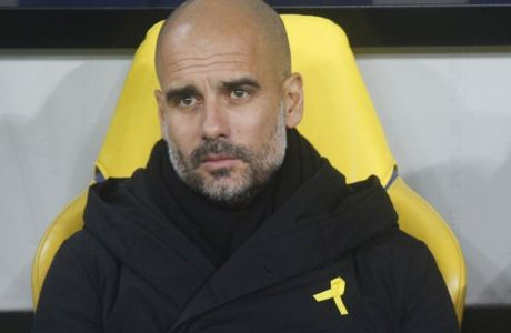 FILE - In this Wednesday, Dec. 6, 2017 file photo, Manchester City coach Josep Guardiola looks on during their Champions League group F soccer match against Shakhtar Donetsk at the Metalist Stadium in Kharkiv, Ukraine. Guardiola has said he wears a yellow ribbon is a gesture of support for imprisoned politicians Jordi Cuixart and Jordi Sanchez, who remain incarcerated amid the row over Catalan independence.  Mourinho said on Friday, Dec. 8 Guardiola was within his rights as a normal citizen to show his political belief and ideology, but doubted if it should be tolerated by UEFA.(AP Photo/Efrem Lukatsky, file)