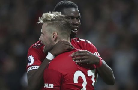Manchester United's Luke Shaw, front, is hugged and congratulated by Manchester United's Paul Pogba, after he scored his sides second goal of the game during the English Premier League soccer match between Manchester United and Leicester City at Old Trafford, in Manchester, England, Friday, Aug. 10, 2018. (AP Photo/Jon Super)