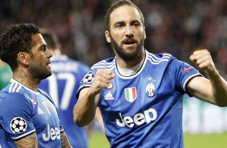 Juventus' Gonzalo Higuain, right, celebrates with his teammate Dani Alves after scoring during the Champions League semifinal first leg soccer match between Monaco and Juventus at the Louis II stadium in Monaco, Wednesday, May 3, 2017. (AP Photo/Claude Paris)