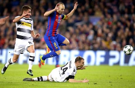 Barcelona's Andres Iniesta, top, jumps over Moenchengladbach's Tony Jantschke during the Champions League, Group C, soccer match between FC Barcelona and Borussia Moenchengladbach at the Camp Nou stadium in Barcelona, Spain, Tuesday Dec. 6, 2016. (AP Photo/Manu Fernandez)
