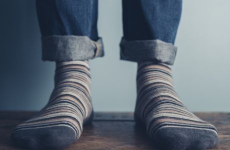 The feet of a man standing on a wooden floors wearing stripey socks
