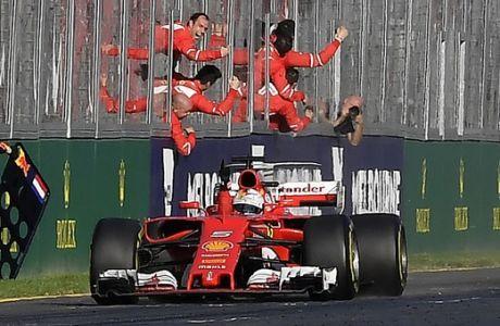 Ferrari driver Sebastian Vettel of Germany races past his celebrating team on the way to winning the Australian Formula One Grand Prix in Melbourne, Australia, Sunday, March 26, 2017. (AP Photo/Andy Brownbill)