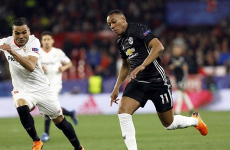 Manchester United's Anthony Martial, right, runs with the ball during the Champions League round of sixteen first leg soccer match between Sevilla FC and Manchester United at the Ramon Sanchez Pizjuan stadium in Seville, Spain, Wednesday, Feb. 21, 2018. (AP Photo/Miguel Morenatti)