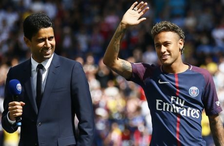 Brazilian soccer star Neymar waves to fans next to PSG president Nasser Ghanim Al-Khelaïfi at the Parc des Princes stadium in Paris, Saturday, Aug. 5, 2017, during his official presentation to fans ahead of Paris Saint-Germain's season opening match against Amiens. Neymar would not play in the club's season opener as the French football league did not receive the player's international transfer certificate before Friday's night deadline. The Brazil star became the most expensive player in soccer history after completing his blockbuster transfer from Barcelona for 222 million euros ($262 million) on Thursday. (AP Photo/Francois Mori)