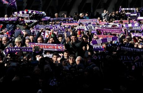 Fans with Fiorentina scarves stand outside the church during the funeral ceremony of Italian player Davide Astori in Florence, Italy, Thursday, March 8, 2018. The 31-year-old Astori was found dead in his hotel room on Sunday after a suspected cardiac arrest before his team was set to play an Italian league match at Udinese. (AP Photo/Alessandra Tarantino)