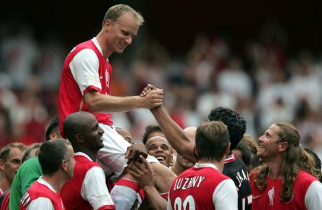 Arsenal's Dennis Bergkamp is carried by players from Arsenal and Ajax at the end of his last game at Arsenal at the Emirates stadium, London, Saturday July 22,  2006.  Saturday's match, the first game to be played in Arsenal's new home stadium, is a tribute match between Arsenal and Ajax to mark the retirement of star striker Dennis Bergkamp.(AP Photo/Tom Hevezi)