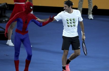 Switzerland's Roger Federer jokes with an actor dressed as Spiderman during the annual Kids Tennis Day event on Rod Laver Arena ahead of the Australian Open tennis championships in Melbourne, Australia Saturday, Jan. 13, 2018. (AP Photo/Ng Han Guan)