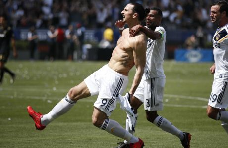Los Angeles Galaxy's Zlatan Ibrahimovic, left, of Sweden, celebrates his debut goal with Ashley Cole and Chris Pontius, right, during the second half of an MLS soccer match against the Los Angeles FC Saturday, March 31, 2018, in Carson, Calif. The Galaxy won 4-3. (AP Photo/Jae C. Hong)