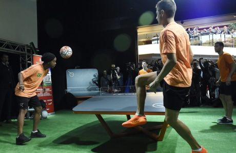 Brazilian professional footballer Ronaldinho, left, tries a newly developed ballgame called teqball during its official presentation in Budapest, Hungary, Tuesday, Oct. 18, 2016. The 36-year-old soccer star, who offered a teqball each to Lionel Messi and Neymar of FC Barcelona in a live video message, is committed to promote the Hungarian sports equipment. The game is played by two opposing teams of two, four or even more persons similarly to football tennis, also known as footnet, but on an arched table. According to a statement by funder and creative director Gabor Borsanyi the long-term goal of the development team is to make teqball a discipline contested in the Summer Olympic Games in twenty to thirty years' time. (Tamas Kovacs/MTI via AP)