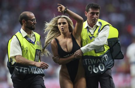 A woman that has invaded the pitch is taken away by security during the Champions League final soccer match between Tottenham Hotspur and Liverpool at the Wanda Metropolitano Stadium in Madrid, Saturday, June 1, 2019. (AP Photo/Francisco Seco)