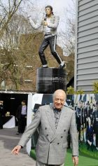 """FILE - This is a Sunday, April, 3  2011 file photo of the then  Fulham Chairman Mohamed Al Fayed, as he reacts after unveiling a statue of the pop legend Michael Jackson, who was a friend of Al Fayed, at Fulham's soccer ground Craven Cottage stadium in London. Standing on Fulham's pitch, on Saturday July 13, 2013, Shad Khan quickly discovered that the issues Premier League owners must tackle extend far beyond football On his first full day running the London club, the trickiest questions Khan had to face were not about transfer targets and the cash available, or goals for the upcoming season. The pressing issue locally for the owner of the NFL's Jacksonville Jaguars was about Michael Jackson. Yes, the late """"King of Pop.""""One of the most contentious decisions by Mohamed Al Fayed during his 18 years owning Fulham was to erect a statue of Jackson outside Fulham's Craven Cottage ground. Al Fayed warned Khan jokingly on Saturday that he'd rip the American's trademark moustache off if the statue was removed. Khan realized that it's a delicate issue, saying he'll """"listen to the fans, then decide."""" (AP Photo/Alastair Grant, File)"""