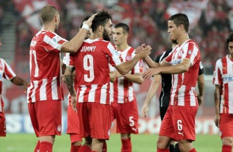 Olympiacos Jimmy Durmaz from Sweden, center no. 9, is congratulated by his teammate Ibrahim Afellay of the Netherlands after scoring the second goal of his team against OFI during a Greek Soccer League match at the Georgios Karaiskakis stadium in the port of Piraeus, near Athens on Saturday, Sept. 13, 2014. (AP Photo/Thanassis Stavrakis)