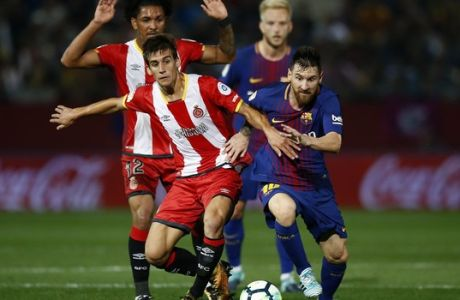 FC Barcelona's Lionel Messi, right, duels for the ball against Girona's Pere Pons during the Spanish La Liga soccer match between Girona and FC Barcelona at the Montilivi stadium in Girona, Spain, Saturday, Sept. 23, 2017. (AP Photo/Manu Fernandez)