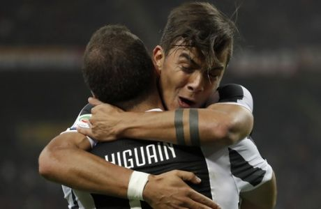 Juventus' Paulo Dybala hugs teammate Gonzalo Higuain who scored his side's first goal during a Serie A soccer match between AC Milan and Juventus, at the Milan San Siro stadium, Italy, Saturday, Oct. 28, 2017. (AP Photo/Luca Bruno)